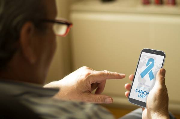 business concept: man with World Cancer Day background on screen phone at home. All screen graphics are made up.